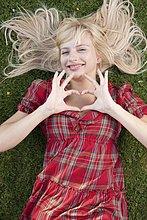 Lächelnde blonde Frau im Gras formt ein Herz mit ihren Händen