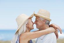 Älteres Paar mit Sonnenhüten küsst sich am Strand