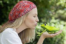 Junge Frau küssen eine Frosch-Spielzeug
