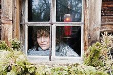 Österreich, Salzburger Land, Flachau, Junge Frau im Winter durchs Fenster blickend