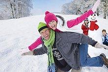 Mann mit üppiger Frau auf dem Rücken und Kindern mit Schneemann im Hintergrund