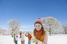 Porträt der Familie, die Schneebälle ins Feld wirft