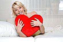 Junge Frau hält ein Herzkissen