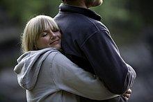 Junge Frau umarmt ihren Freund im Freien
