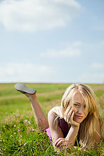Junge Frau liegen auf ihrer Vorderseite in einem Feld, lächelnd