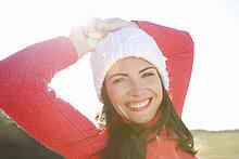 Lächelnde Frau mit den Händen auf dem Kopf tragen Wollen Hut