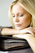 Blonde Frau mit geschlossenen Augen stützt sich auf Aktenordnern auf