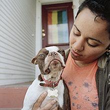 Eine Frau hält ihren Hund, den Mund.
