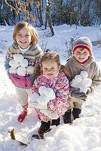 Porträt von lächelnden Kindern mit Schneebällen