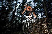 Mountainbikefahrer auf einer Holzbrücke, Südtirol, Italien