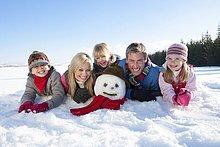 Porträt einer lächelnden Familie im Schnee mit Schneemann