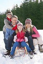 Portrait of smiling Familie sitzen auf Schlitten im Schnee