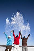 Menschen spielen mit Schnee im Feld