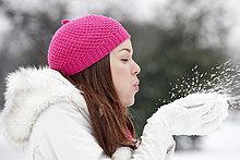Eine junge Frau, die eine Handvoll Schnee weht