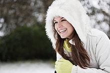 Eine junge Frau, hocken im Schnee, lächelnd