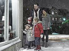 Familie bewundert Weihnachtsfenster im Schnee