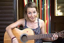 Woman plucking guitar in allotment garden
