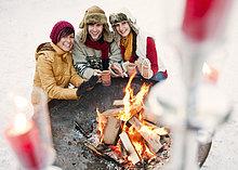 Österreich, Salzburg, Mann und Frau beim Feuer auf dem Weihnachtsmarkt, lächelnd