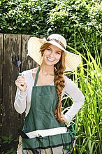 Lächelnde junge Frau mit Sonnenhut und Schürze im Garten
