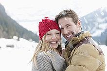 Lächelndes Paar umarmt sich im Schnee