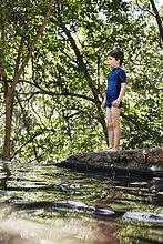 Junge steht am Fluss im Wald