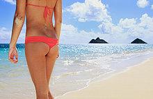 Hawaii, Oahu, Lanikai, Ansicht von hinter einer Frau mit den Mokulua Inseln im Hintergrund.