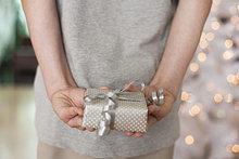 Mädchen hält Geschenk hinter dem Rücken
