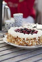 Frischer Kuchen mit Beerenobstbelag auf Holztisch serviert