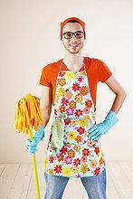 Lächelnder junger Mann beim Hausputz