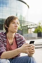 Nachdenklicher junger, männlicher Studierender mit dem Handy im Hintergrund