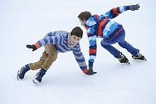 Zwei Jungen laufen Schlittschuh auf einem gefrorenen See