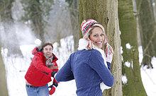 Ausgelassenes junges Paar macht eine Schneeballschlacht