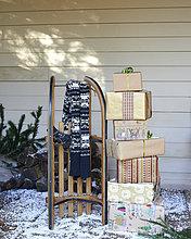 Schal, Holzschlitten und Weihnachtsgeschenke auf verschneiter Veranda