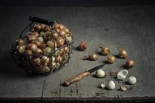 Korb mit Perlzwiebeln mit Messer auf Holzplatte, Nahaufnahme