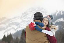 Glückliche Frau mit Geschenk und umarmendem Mann mit Bergen im Hintergrund
