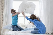 Mädchen Kissenschlacht auf dem Bett