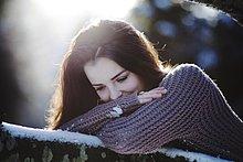 Junge Frau liegt auf einem Baumstamm im Schnee