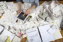 Frau mit Rechnungen und Kassenbons auf einem Schreibtisch, für die Steuererklärung, rechnet auf einem Tablet-PC
