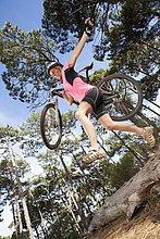 Frau springt mit dem Mountainbike über den Baumstamm im Wald