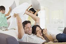 Familie genießt Kissenschlacht im Wohnzimmer