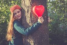 Portrait,Jugendlicher,umarmen,lächeln,Baum,Luftballon,Ballon,Form,Formen,herzförmig,Herz,Mädchen