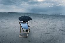 reife Frau sitzt auf Liegestuhl am stürmischen Strand, unter dem Regenschirm