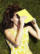 hinter,liegend,liegen,liegt,liegendes,liegender,liegende,daliegen,Frau,Schönheit,lachen,Buch,aufspüren,gelb,grün,Gras,Taschenbuch,nachsehen