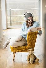 sitzend,junge Frau,junge Frauen,Stuhl,lächeln,Kopfhörer,Tablet PC