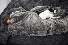 Junge Frau in Pelzdecke gewickelt, entspannt auf der Couch mit Hund