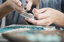 Nahaufnahme einer Frau, die mit einer Zange an einer Perlenkette arbeitet.