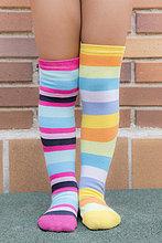 Füße eines Mädchens mit unterschiedlich gestreiften farbigen Socken