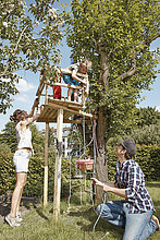 Family playing at tree house in garden