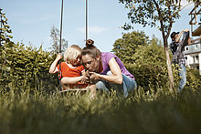 Mother caring for injured daughter in garden