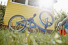 Boy repairing bicycle in garden